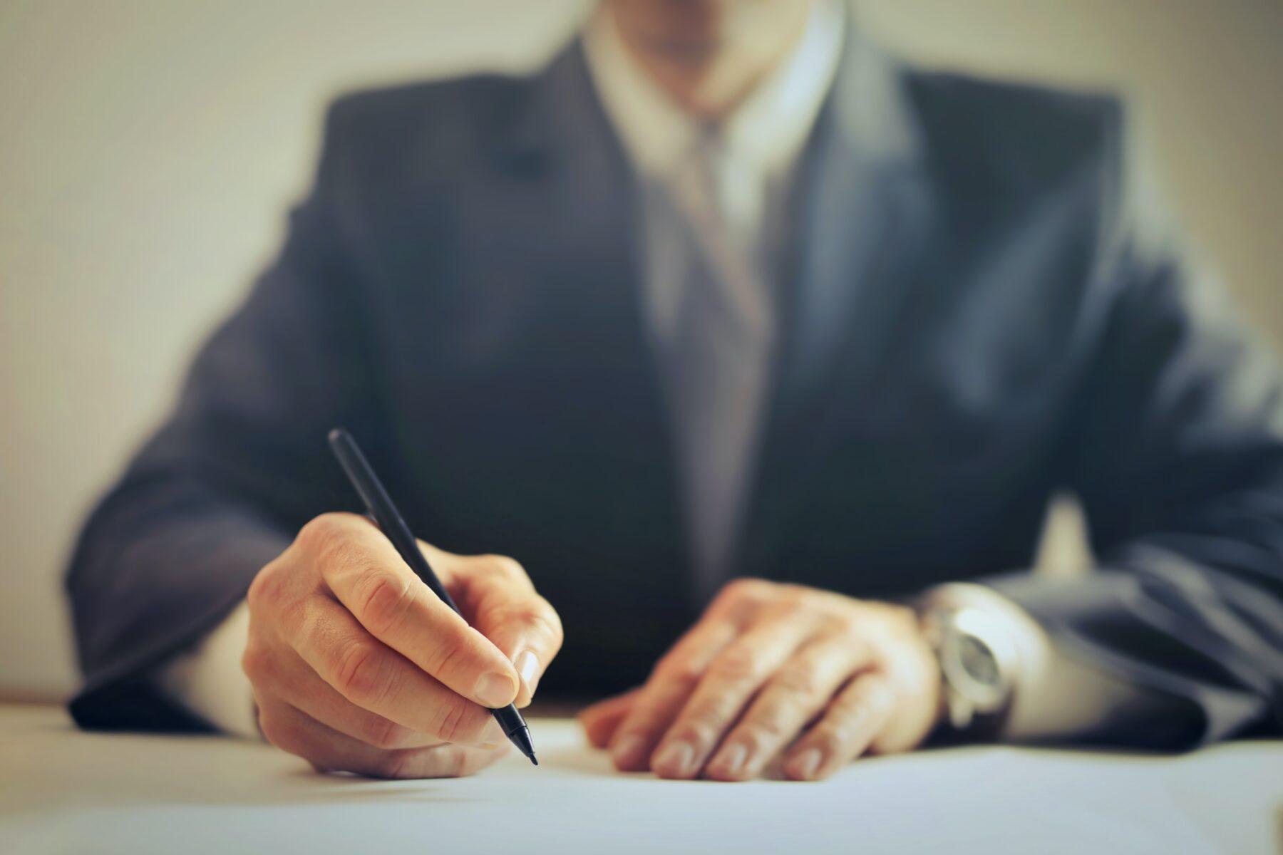 Advocaat achter bureau die papieren tekent.